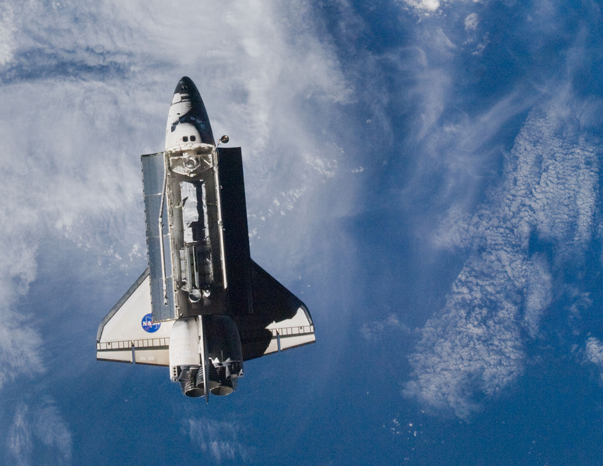 Space Shuttle Discovery approaches the International Space Station (NASA image iss018e042051)