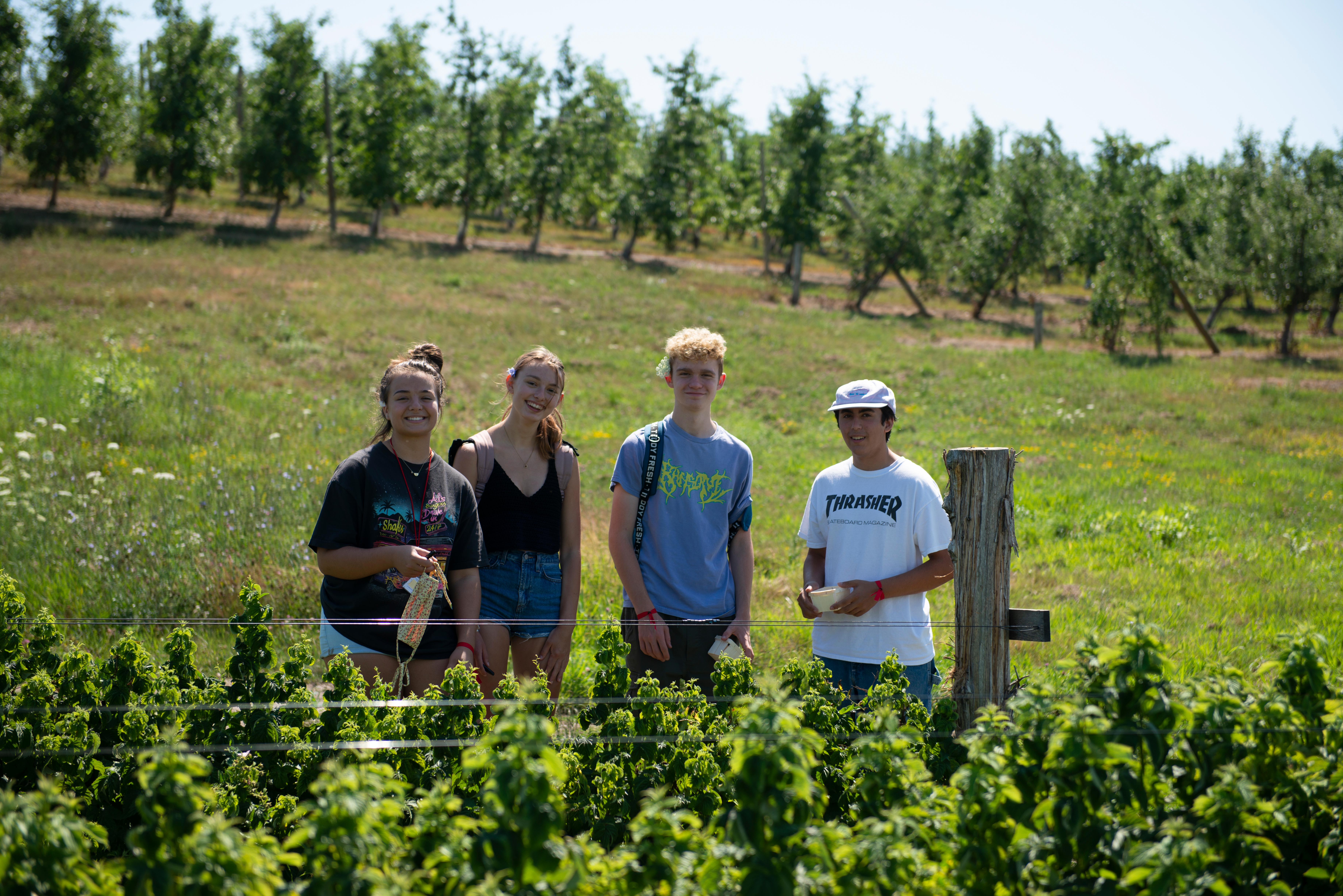 Smiling students standing in Vermont orchard facing camera