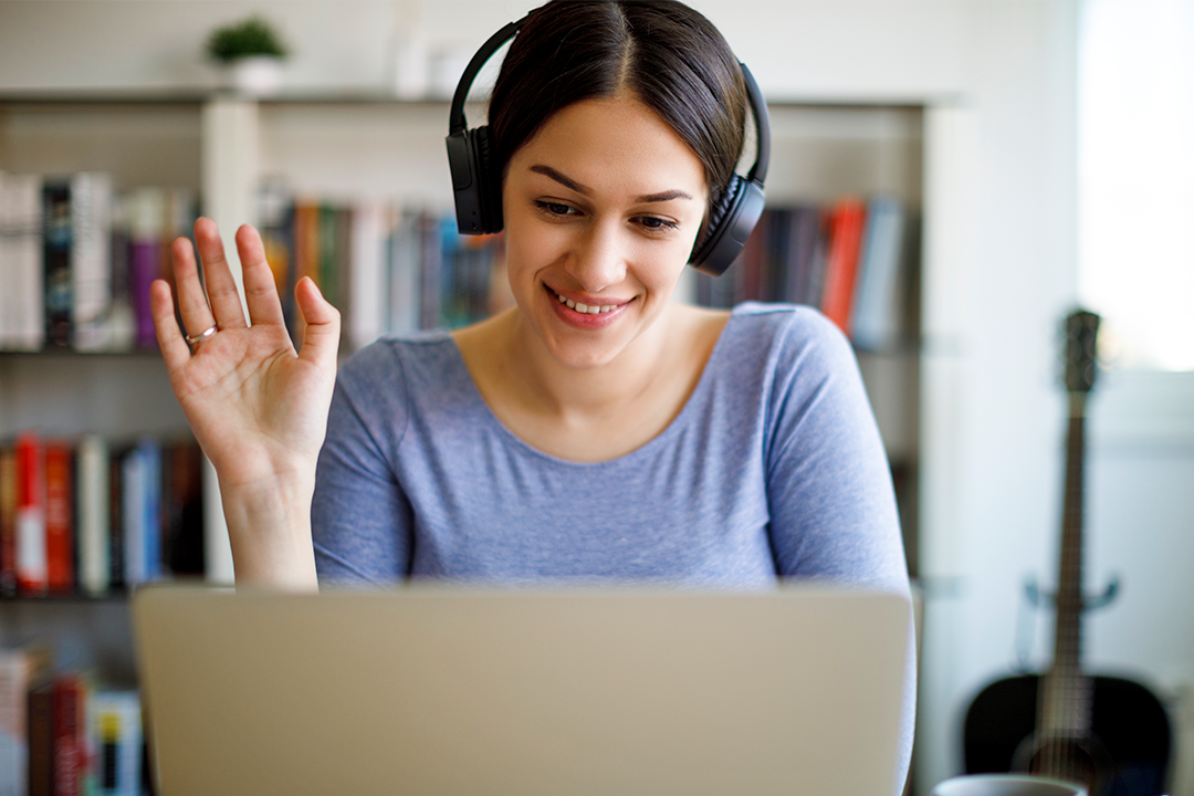 Young female student sitting wearing headphones waving and looking at laptop